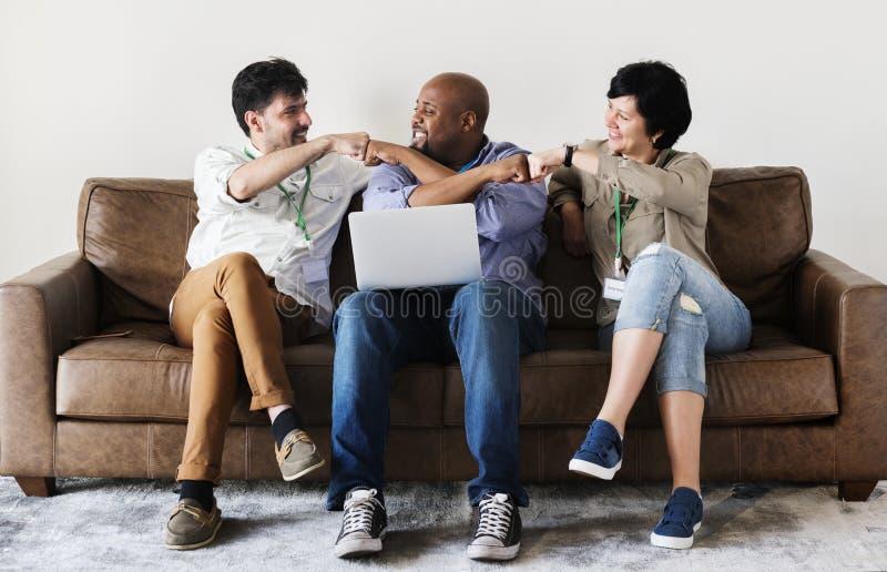 Trabajadores que trabajan en el ordenador portátil junto fotos de archivo libres de regalías