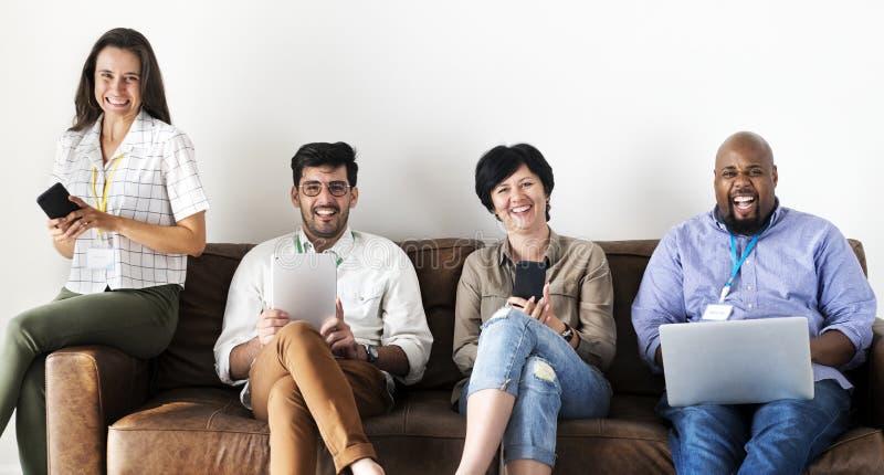 Trabajadores que trabajan en el ordenador portátil en el sofá foto de archivo libre de regalías