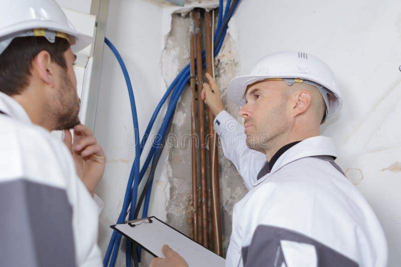 Trabajadores que trabajan en el tubo del pvc fotos de archivo