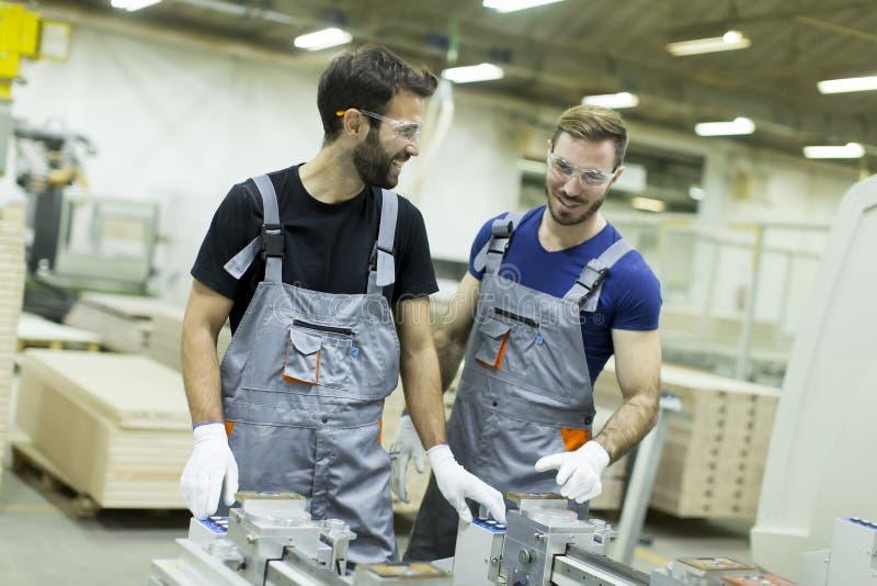 Trabajadores que trabajan en industria de los muebles y que crean el cust imágenes de archivo libres de regalías