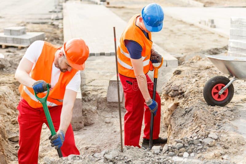 Trabajadores que vierten la arena en la carretilla imagen de archivo libre de regalías