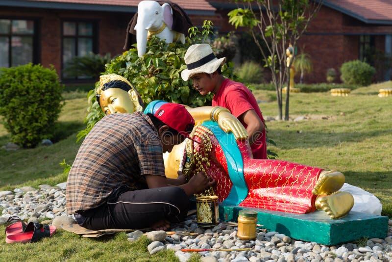 Trabajadores restorating las estatuas de Buda en Lotus Stupa - Lumbini, Nepal foto de archivo