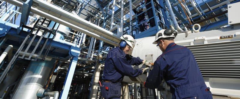 Trabajadores y tuberías del petróleo fotos de archivo