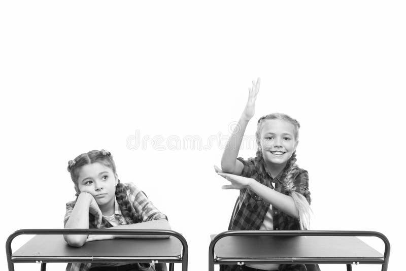 Trabajando duro en su conocimiento Niños pequeños y adorables que pasan la prueba de conocimiento en los escritorios escolares Co imagen de archivo libre de regalías