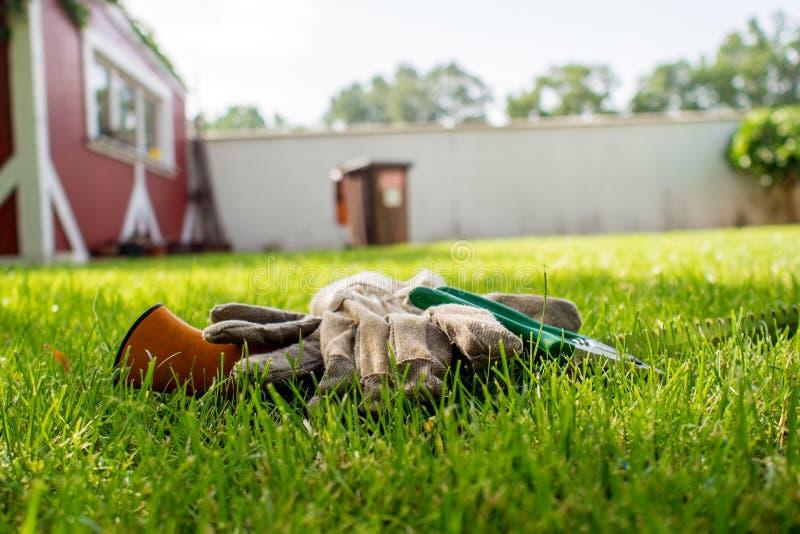 Trabajando en jardín, utensilios de jardinería que ponen en hierba verde fotografía de archivo