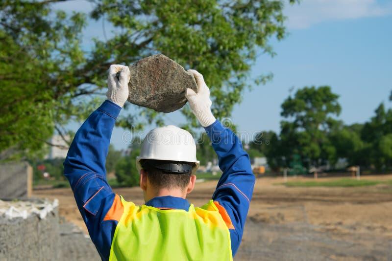 Trabajando en un casco blanco, sosteniendo una piedra con dos manos, sobre la cabeza protegida, vista posterior imágenes de archivo libres de regalías