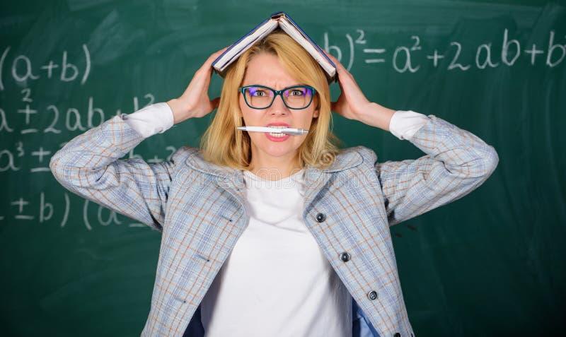 Trabaje demasiado y falta de ayuda que conduce al profesor de la profesión Mujer del profesor con el fondo de la pizarra del libr fotos de archivo libres de regalías