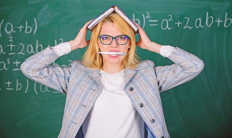 Trabaje demasiado y falta de ayuda que conduce al profesor de la profesi?n Mujer del profesor con el fondo de la pizarra del libr fotografía de archivo