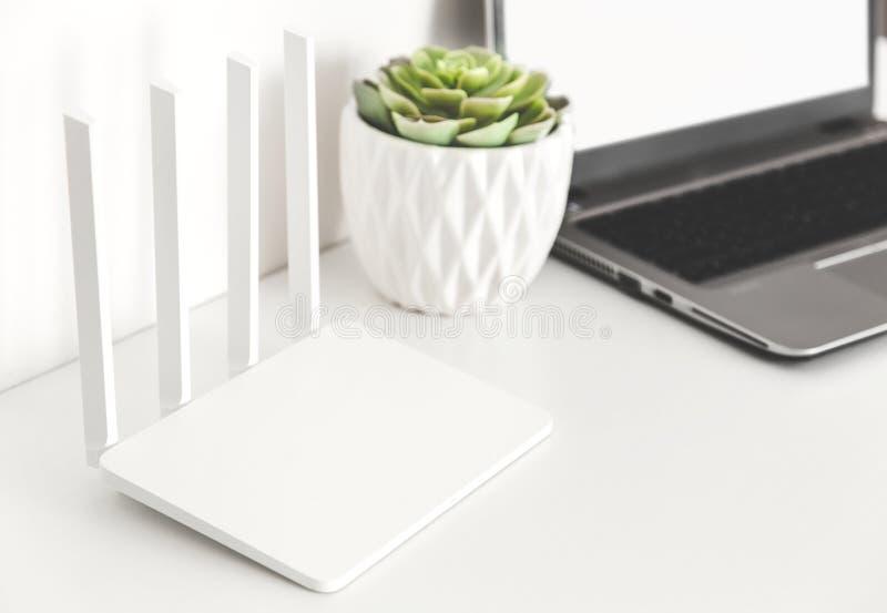 Trabaje en casa o en la oficina en el ordenador portátil vía el router de Wi-Fi independiente fotos de archivo libres de regalías