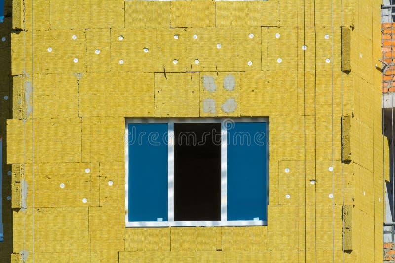 Trabaje en las paredes externas del aislamiento de las lanas de cristal y enyese foto de archivo libre de regalías