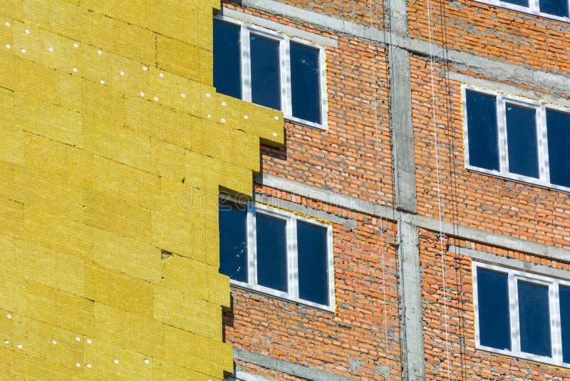 Trabaje en las paredes externas del aislamiento de las lanas de cristal y enyese imagen de archivo