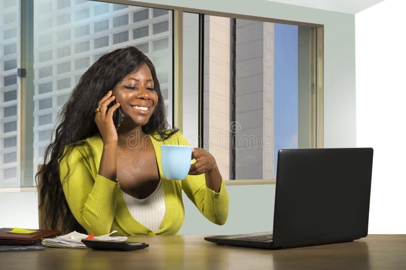 Trabajo afroamericano negro atractivo de la empresaria confiado en el escritorio del ordenador que habla en el teléfono móvil sat imagenes de archivo