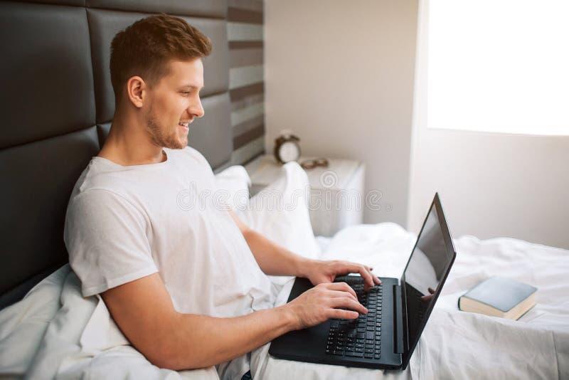 Trabajo agradable alegre del hombre joven en la cama moring temprano Ordenador portátil y tipo del control del individuo en el te imagenes de archivo