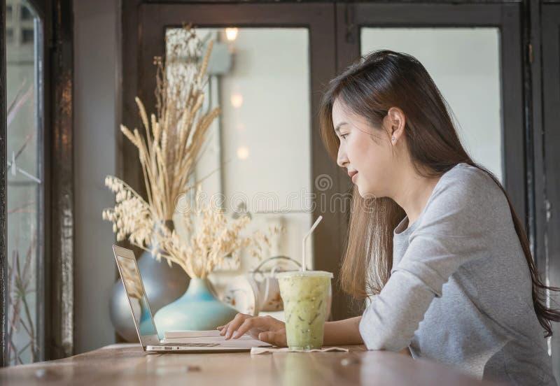 Trabajo asiático de la mujer del primer con el ordenador en el escritorio contrario de madera en cafetería con la cara feliz en b foto de archivo