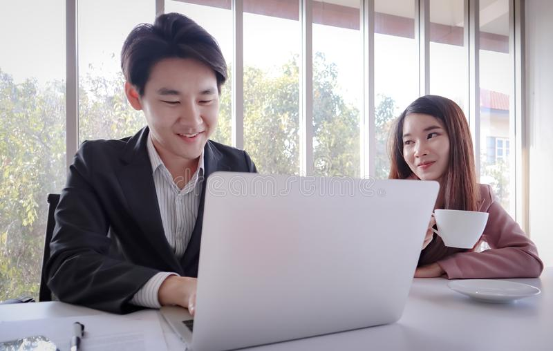 Trabajo asiático joven del hombre de negocios con el ordenador portátil en la oficina fotos de archivo libres de regalías