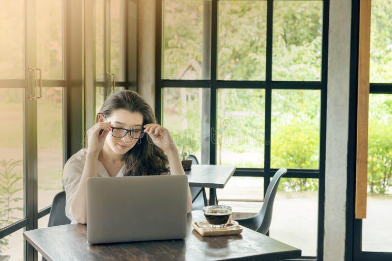 Trabajo asiático joven del negocio de la mujer en mirada de Ministerio del Interior en el ordenador portátil con el pensamiento C fotos de archivo