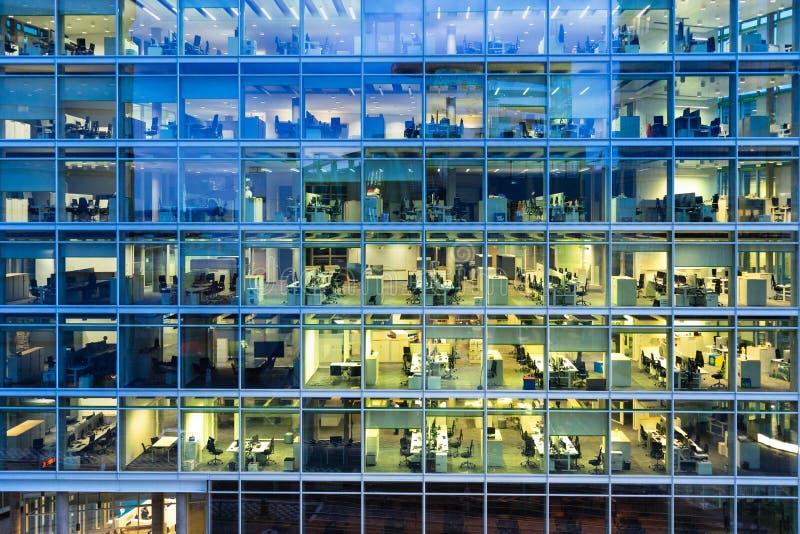 Trabajo atrasado: espacios de oficina iluminados en un edificio moderno por la tarde fotos de archivo