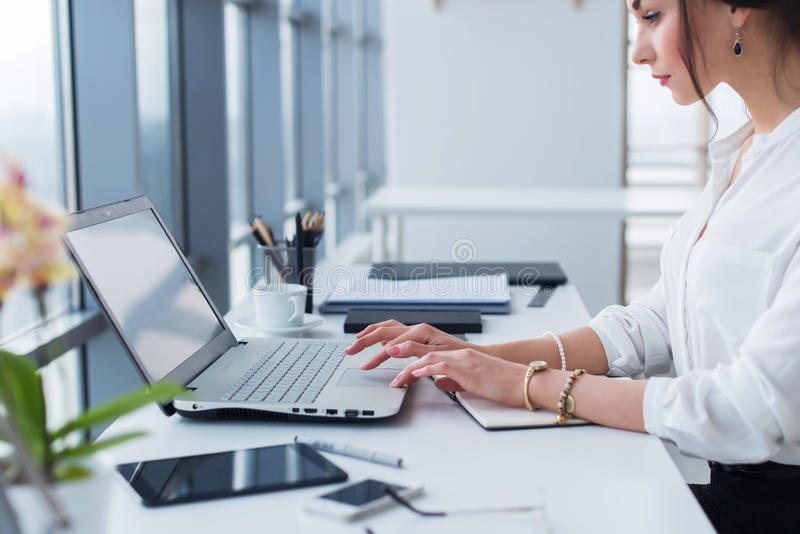 Trabajo auxiliar femenino atractivo, mecanografiando, usando el ordenador portátil, concentrado, mirando el monitor oficina fotografía de archivo libre de regalías