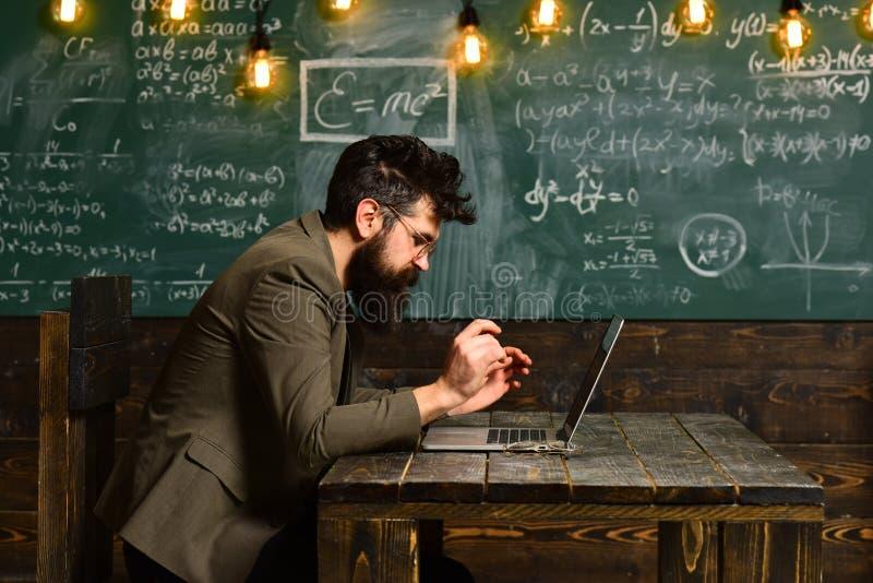 Trabajo barbudo del hombre sobre el ordenador portátil en sala de clase Hombre con la barba larga con el ordenador en la pizarra  fotografía de archivo libre de regalías