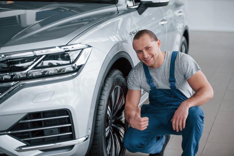 Trabajo bien hecho Después de la reparación profesional Hombre mirando un auto de color plata perfectamente pulido imagen de archivo