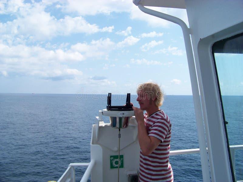 Trabajo con el dispositivo del acimut en buque mercante cerca de la costa foto de archivo