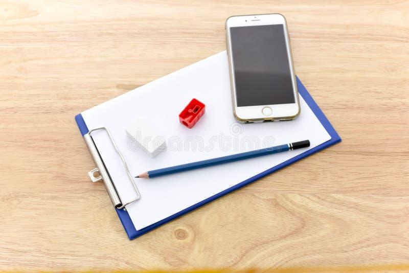 Trabajo con el teléfono móvil y el tablero azul de la libreta del camarero con P imagen de archivo libre de regalías