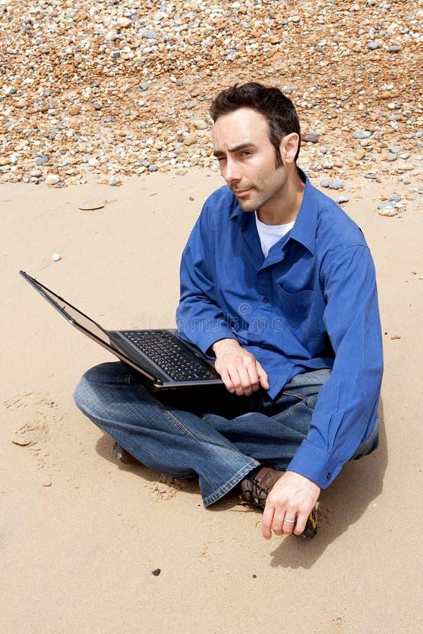 Trabajo con la computadora portátil en la playa imagenes de archivo
