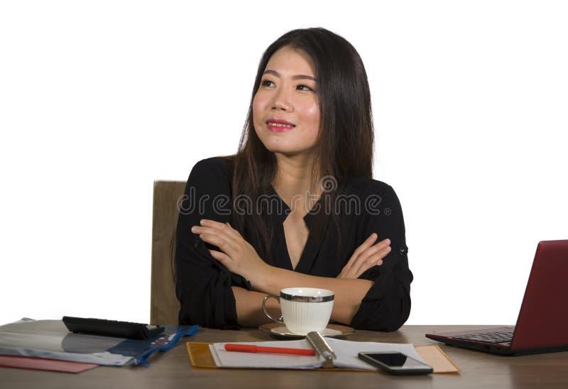 Trabajo coreano asiático acertado hermoso y feliz joven de la empresaria relajado en la sonrisa del escritorio del ordenador de o foto de archivo libre de regalías