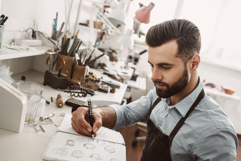 Trabajo creativo Retrato del joyero barbudo joven que dibuja un bosquejo de un nuevo anillo imagen de archivo