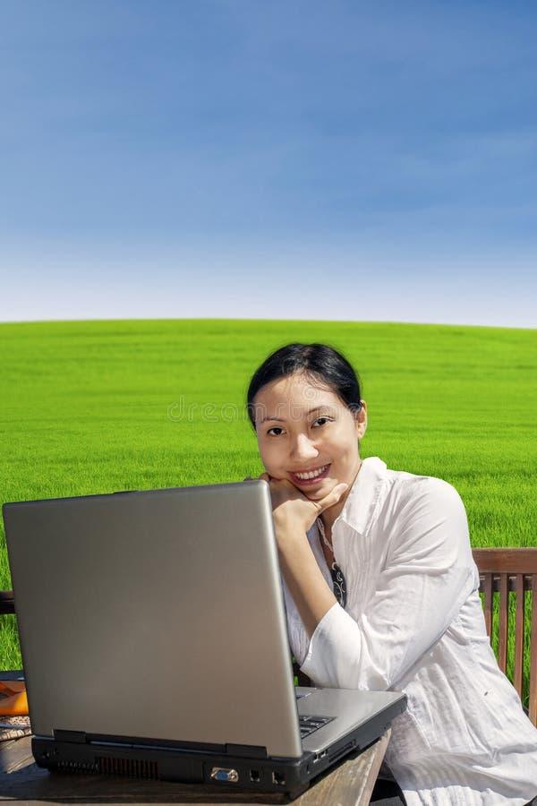 Trabajo de la empresaria con el ordenador portátil en parque fotografía de archivo