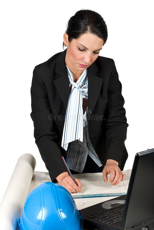Trabajo de la mujer del ingeniero en planes de la oficina y del gráfico foto de archivo