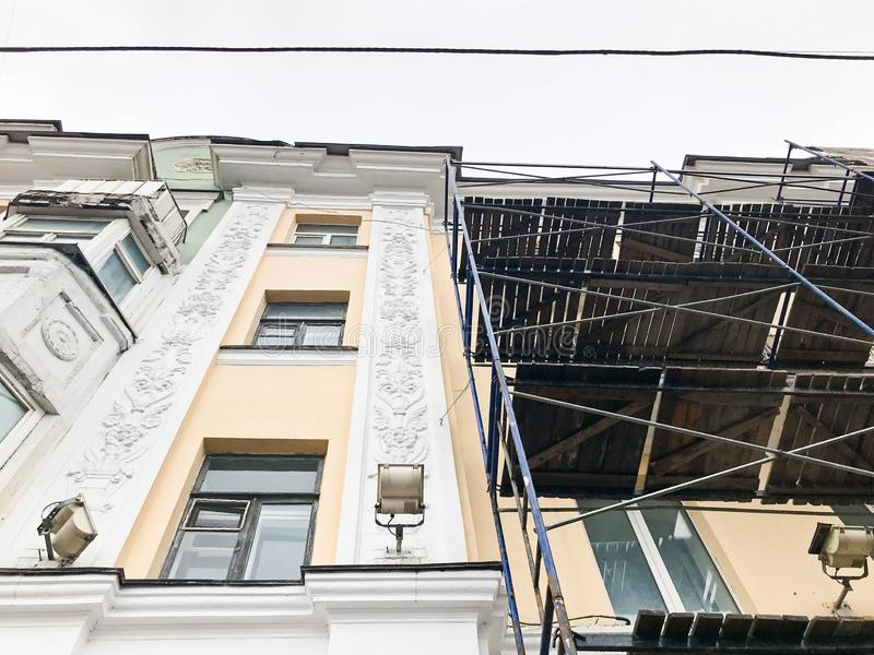 Trabajo de la reparación sobre la fachada del edificio con la ayuda del andamio de madera, estructuras, restauración de la casa v foto de archivo