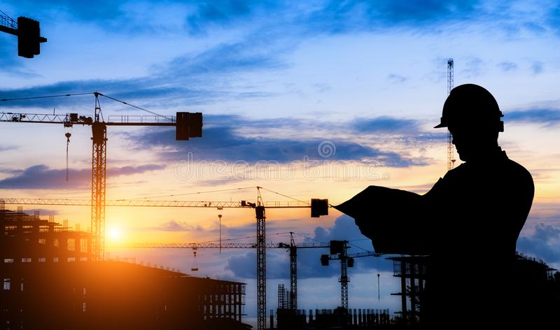 Trabajo de la situación del ingeniero de la silueta sobre la construcción imagen de archivo libre de regalías