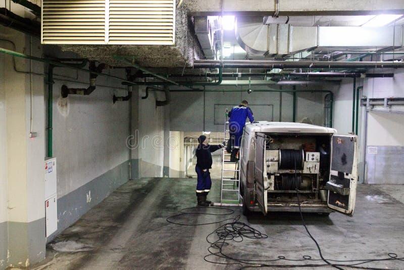 Trabajo de limpio industrial de las aguas residuales, fontanería, ventilación en base del coche en el edificio Dos hombres, speci imágenes de archivo libres de regalías
