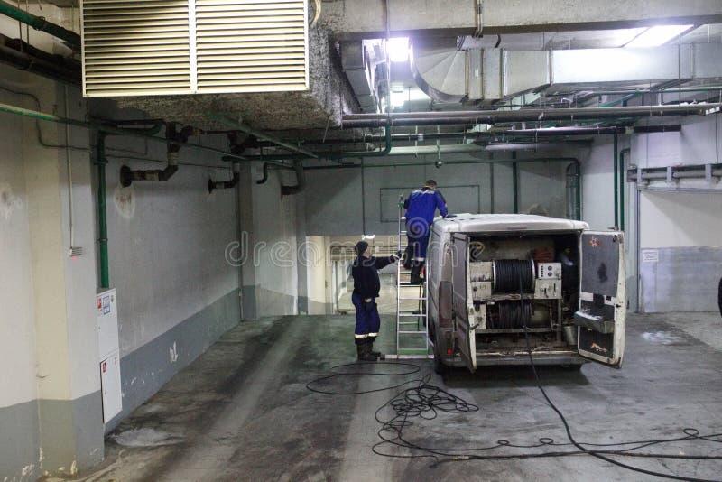 Trabajo de limpio industrial de las aguas residuales, sondeando en base del coche en el edificio Dos hombres, vehículo especial,  imagen de archivo libre de regalías