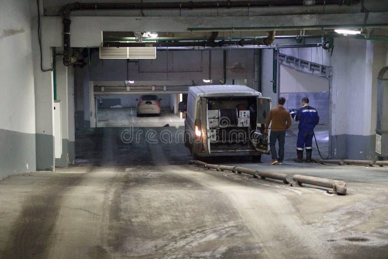 Trabajo de limpio industrial de las aguas residuales, sondeando en base del coche en el edificio Dos hombres, vehicl especial foto de archivo