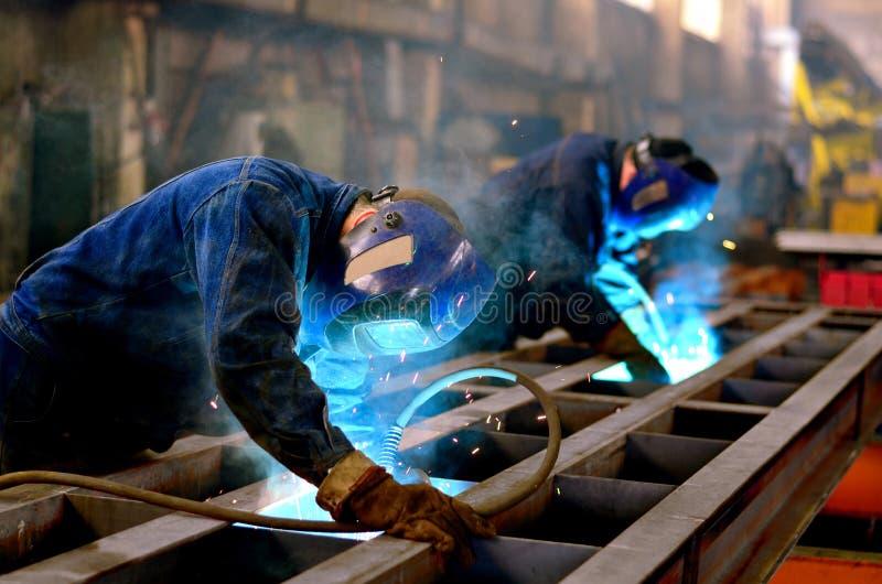 Trabajo de los soldadores en la fábrica fotografía de archivo