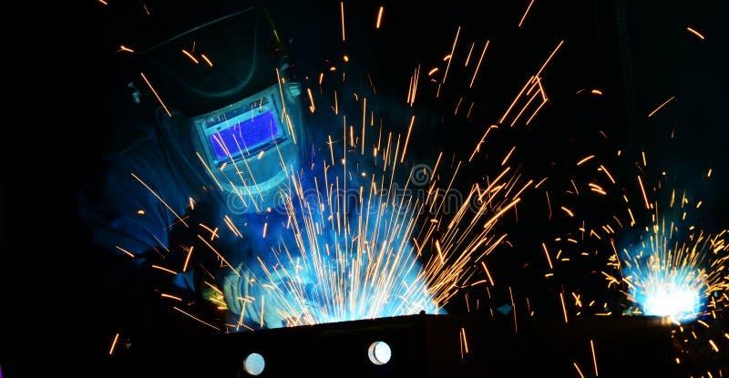 Trabajo de los soldadores en la fábrica foto de archivo