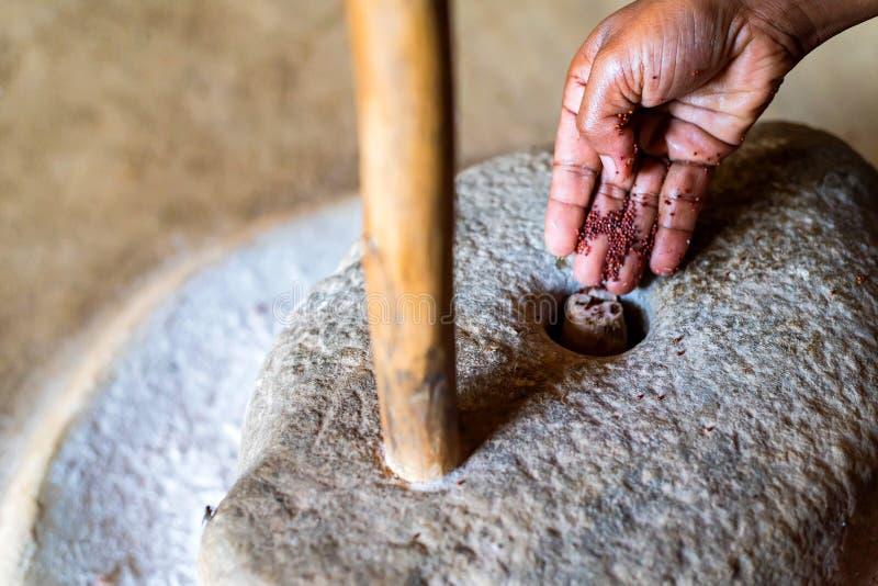 Trabajo de manos con la piedra de molino para moler sorhum en casa srilanquesa fotos de archivo