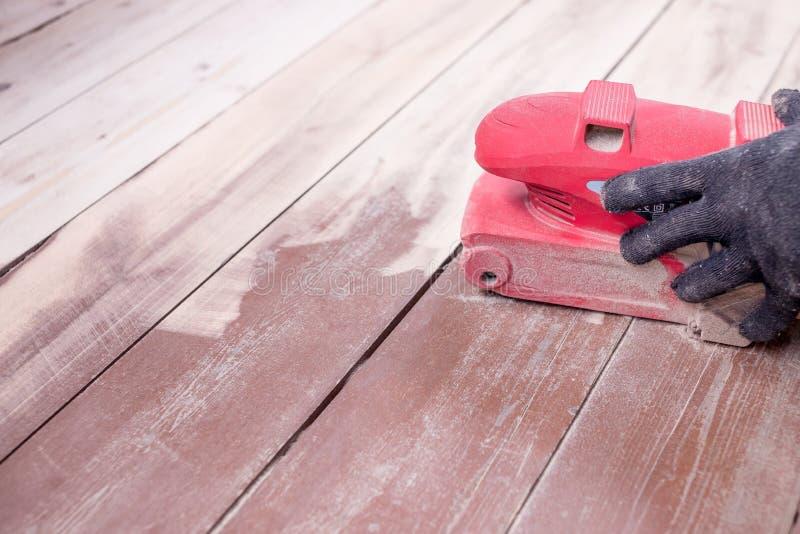 Trabajo de mantenimiento de pulido del piso de madera por la máquina de pulir Las manos de los hombres con los guantes reparan en foto de archivo