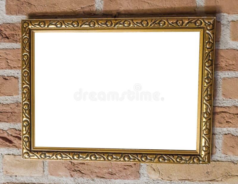 Trabajo de pintura en blanco de oro del marco del viejo vintage del cuadrado que cuelga en un cierre de la pared de ladrillo para foto de archivo