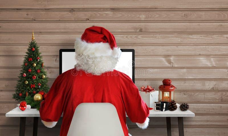 Trabajo de Santa Claus sobre un ordenador en su oficina Respuesta en letras y tarjetas de felicitación vía correo electrónico fotografía de archivo