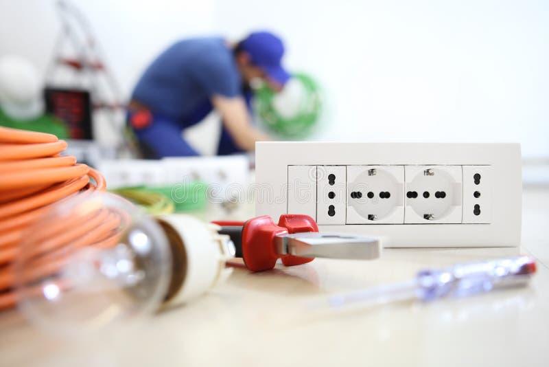 Trabajo del electricista con el equipo eléctrico en el bulbo del primero plano, las herramientas y el zócalo, circuitos eléctrico imagenes de archivo