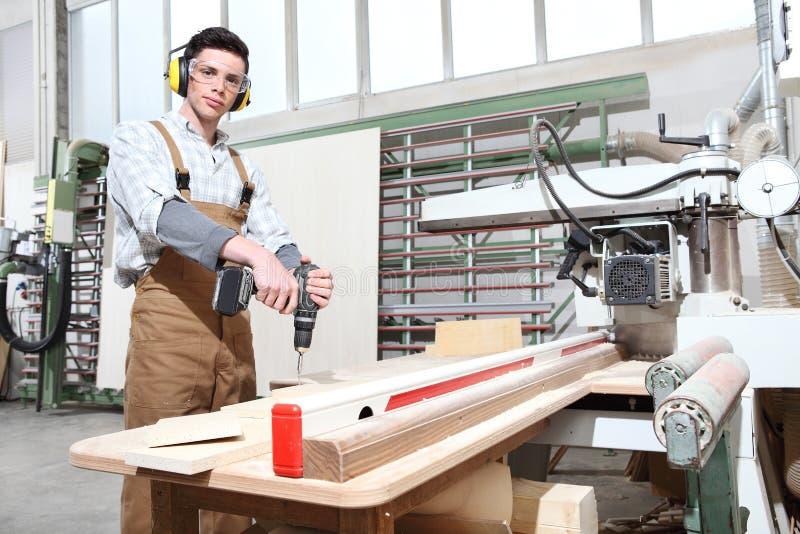 Trabajo del hombre del carpintero en la carpintería, con el tornillo sin cuerda del conductor del taladro un tablero, protegido c fotos de archivo