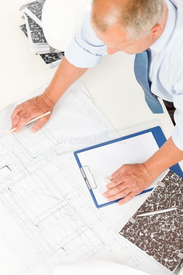 Trabajo del hombre mayor sobre planes de la construcción de los modelos imagen de archivo libre de regalías