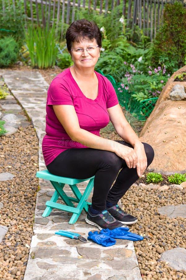 Trabajo del jardín Retrato de la mujer mayor sonriente positiva que tiene un resto después de salas de despiece en ella imagen de archivo libre de regalías
