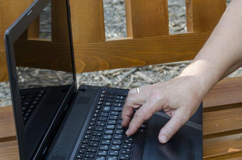 Trabajo del operador sobre el ordenador portátil abierto en un banco de madera foto de archivo libre de regalías