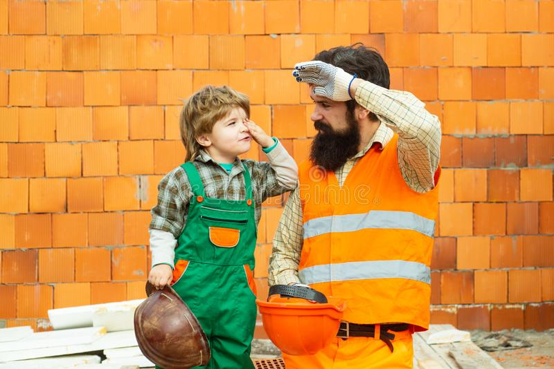 Trabajo duro D?a laborable Un equipo de constructores está cansado en el trabajo Un hombre y un muchacho en un traje de construct fotografía de archivo