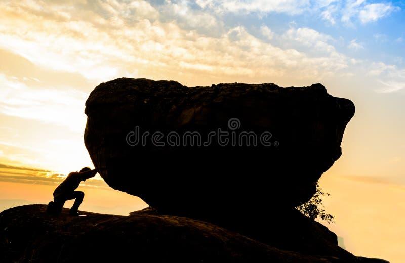 Trabajo duro La persona rueda la roca en la montaña imagenes de archivo