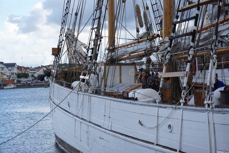 Trabajo duro sobre el velero y la nave anclados fotografía de archivo